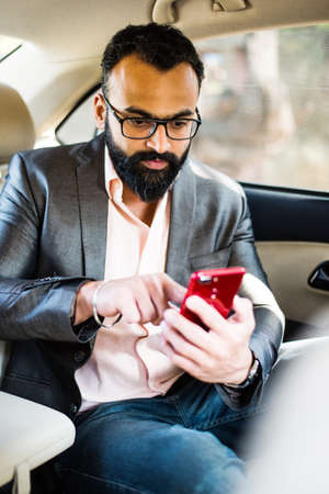 Indianasian young businessman using smart phone inside the car, selective focus