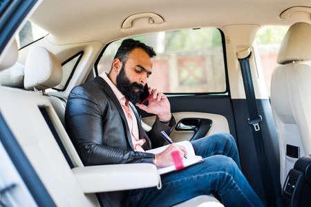 Indian/asian young businessman using smart phone inside the car, selective focus Standard-Bild