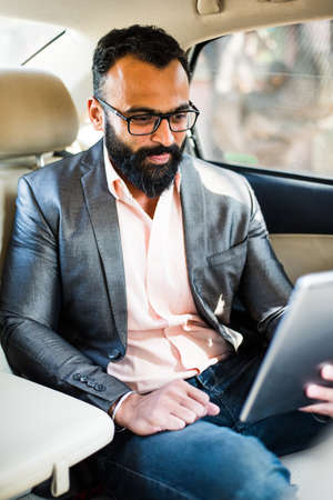 Indianasian young businessman using Tablet computertab while seated on back seat, selective focus