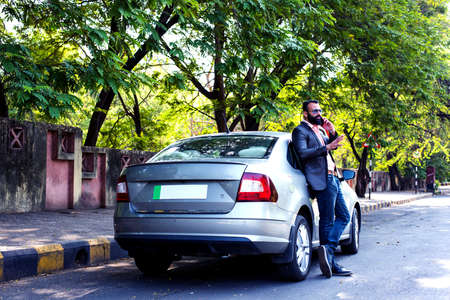 Indianasian young businessman using smart phone near car, outside view. selective focus