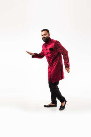 Bearded Indian Man performing desi dance steps while wearing traditional kurta/sherwani, celebrating wedding or party, isolated over white background Stock Photo