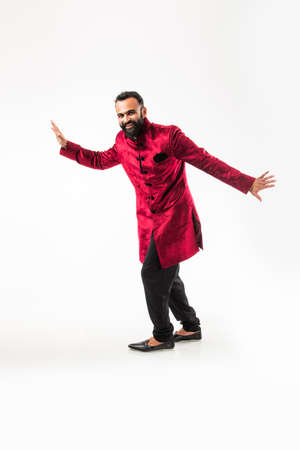 Bearded Indian Man performing desi dance steps while wearing traditional kurtasherwani, celebrating wedding or party, isolated over white background