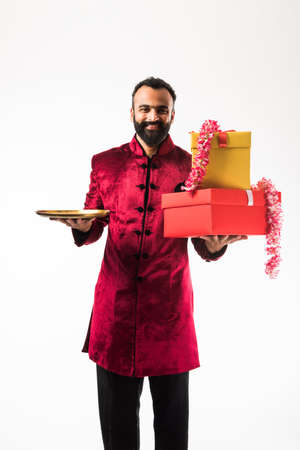 Indian man holding flower garland, gift boxes and empty plate on diwali wedding or festivals while wearing traditional cloths  sherwani , standing isolated over white background
