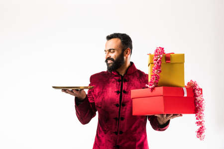 Indian man holding flower garland, gift boxes and empty plate on diwali/ wedding or festivals while wearing traditional cloths / sherwani , standing isolated over white background