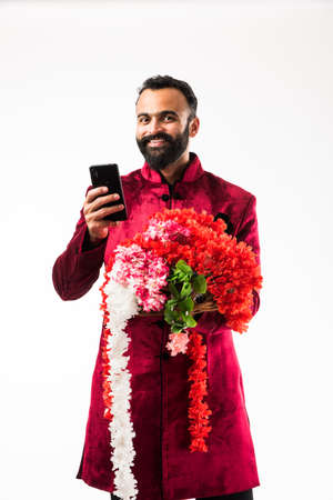 Indian man holding flower garland / series for decoration on diwali/ wedding or festivals while wearing traditional cloths / sherwani , standing isolated over white background