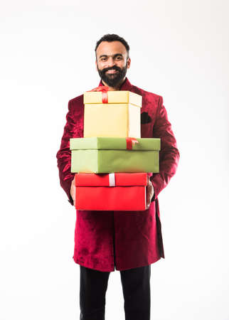 Indian cheerful bearded Man in traditional wearsherwani holding gift box over white background Stok Fotoğraf