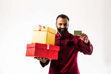 Young happy Indian man with beard holding gift box and empty card while wearing traditional cloths sherwani, standing against white background Stok Fotoğraf