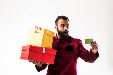 Young happy Indian man with beard holding gift box and empty card while wearing traditional cloths /sherwani, standing against white background