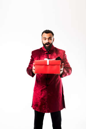Indian cheerful bearded Man in traditional wear/sherwani holding gift box over white background