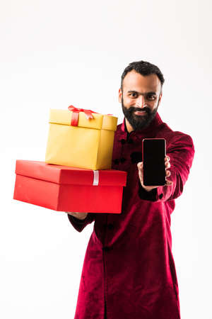 Young happy Indian man with beard holding gift box and mobilesmartphone while wearing traditional cloths sherwani, standing against white background