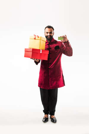 Young happy Indian man with beard holding gift box and empty card while wearing traditional cloths sherwani, standing against white background Stockfoto