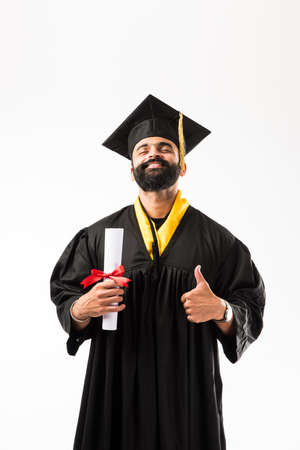 education, graduation and people concept - happy Indian Male graduate student in mortarboard and bachelor gown