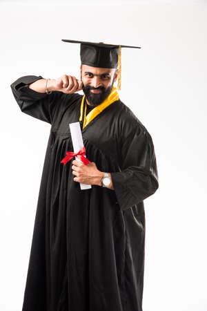 education, graduation and people concept - happy Indian Male graduate student in mortarboard and bachelor gown Stock Photo