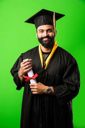 education, graduation and people concept - happy Indian Male graduate student in mortarboard and bachelor gown 版權商用圖片