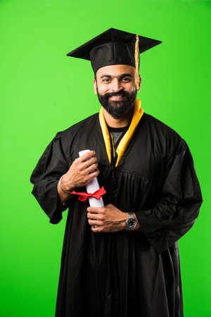 education, graduation and people concept - happy Indian Male graduate student in mortarboard and bachelor gown Banco de Imagens