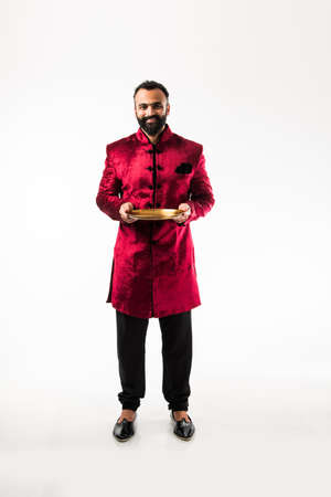Indian Man holding empty plate while wearing traditional Sherwani on Diwali or wedding party, standing isolated over white background
