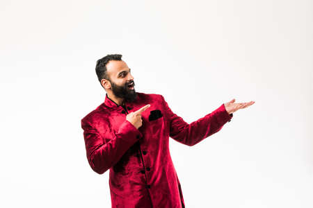 Indian man presenting while wearing traditional sherwani. standing isolated over white background Stockfoto