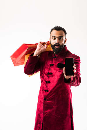 Indian man using mobilesmartphone while holding shopping bags
