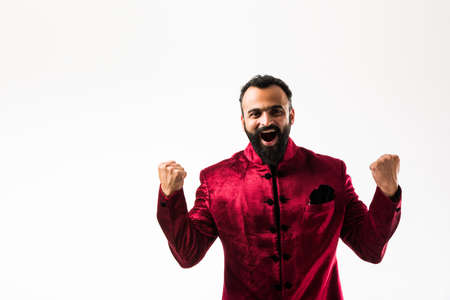Cheerful bearded Indian Man in traditional wear showing success or confidence, selective focus Stock Photo