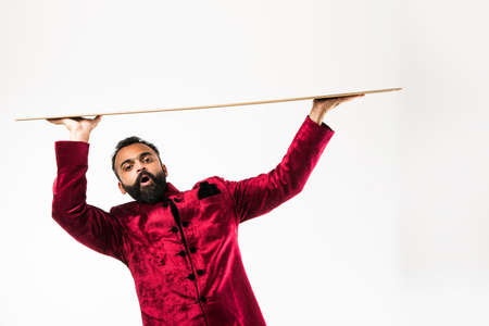 Indian man presenting while wearing traditional sherwani. standing isolated over white background Stock Photo