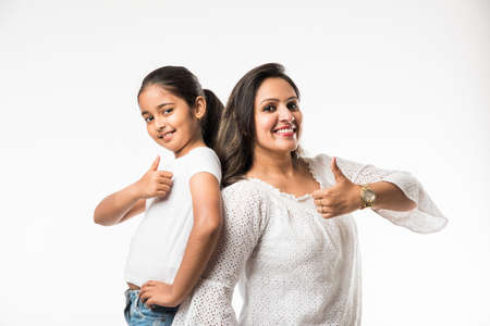 Indian mother daughter on white background hugging, kissing, riding, flying, pointing, presenting over white background