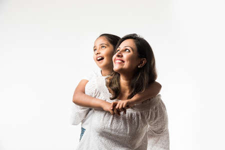 India madre hija sobre fondo blanco abrazos, besos, montar a caballo, volar, señalar, presentar sobre fondo blanco. Foto de archivo