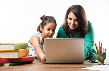 Niña india estudiando con la madre o el maestro en la mesa de estudio con computadora portátil, libros y divertirse aprendiendo