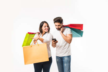 Indian young couple shopping bags and smart phone or mobile, clicking selfie or locating store, standing isolated over white background. selective focus Standard-Bild