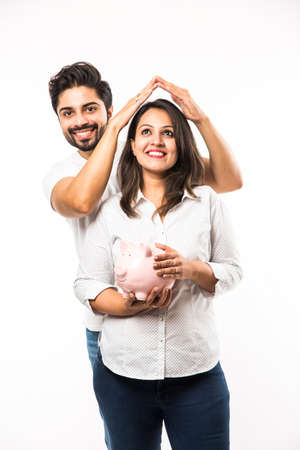 Indian couple with piggy bank standing isolated over white background