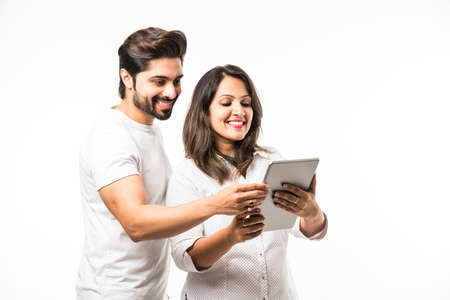 Indian couple using tablet computer while standing isolated over white background