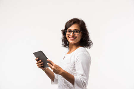 indian lady/women using tablet pc while standing isolated over white background, selective focus Stockfoto