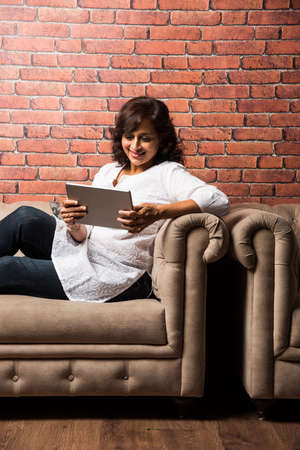 Indian Lady/women using Tablet PC while sitting on sofa/couch, selective focus Stock fotó