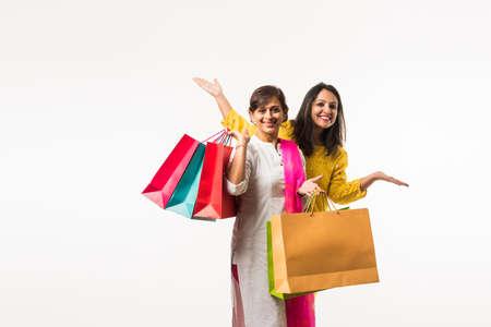 Hija de madre india hermanas compras con bolsas de colores, que se encuentran aisladas sobre fondo blanco. Foto de archivo