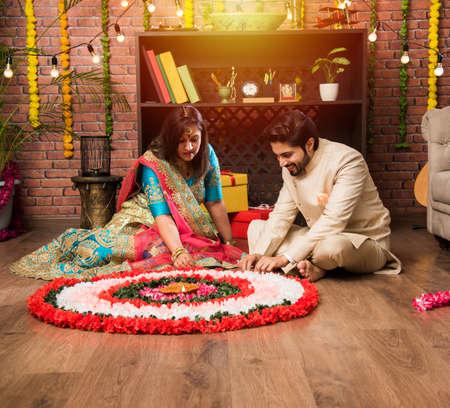 Indian couple making flower Rangoli on Diwali or Onam Festival, taking selfie or holding sweets Stock Photo