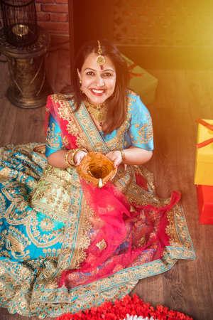 beautiful indian girl holding diya on diwali festival night, top view.selective focus