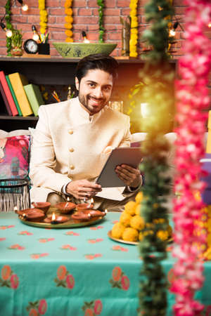 Indian man using tablet touchscreen computer on festival day while wearing traditional outfit. sitting on sofa with gifts and sweets with lighting bokeh