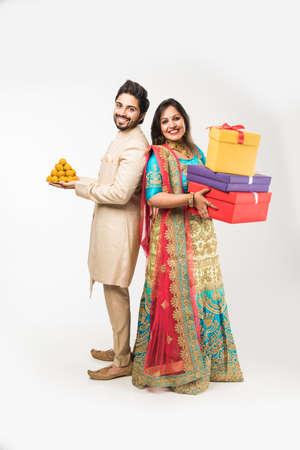 Indisches Paar mit Laddu und Geschenkboxen auf Diwali /festival, stehend auf weißem Hintergrund. traditionelle Kleidung tragen
