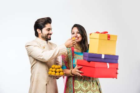 Indisches Paar mit Laddu und Geschenkboxen auf Diwali /festival, stehend auf weißem Hintergrund. traditionelle Kleidung tragen Standard-Bild