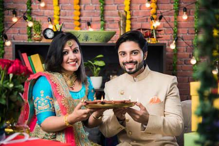 Indian couple with diya, sweets and gifts while celebrating Diwali, Deepavali or Dipavali festival