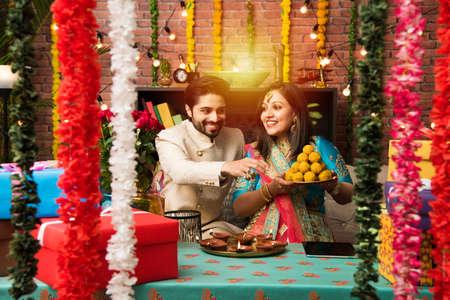 Pareja india con diya, dulces y regalos mientras celebra el festival de Diwali, Deepavali o Dipavali Foto de archivo