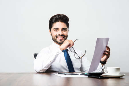 Indian businessman writing a document while sitting at desk or work station