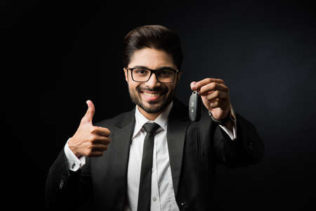 Indian businessman with Car Keys, standing isolated over black background Stock Photo