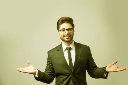 spread both hands by Indian businessman, standing isolated with wide open arms