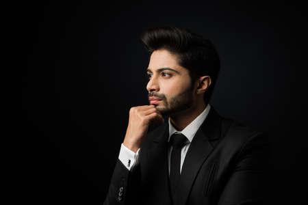 Portrait of Indian Male businessman standing over black background Stock fotó
