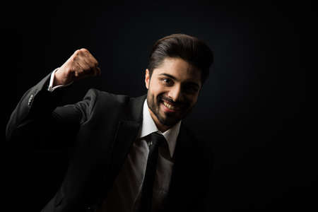 Indian Bearded Male businessman celebrating success with thumbs up or raising fist while standing isolated over black background