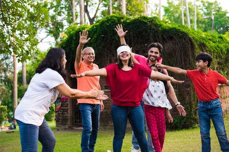 Famiglia indiana che gioca con gli occhi bendati nel parco o in giardino, famiglia asiatica multigenerazionale che gioca a giochi divertenti all'aperto