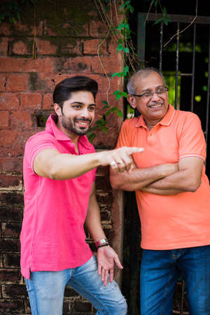 indian / asian senior father son, posing for photograph while wearing jeans and T-shirt, against red brick wall