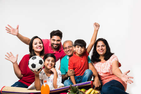 Indian Kids with parents / grandparents, sitting isolated over white background, studio shot Stock Photo