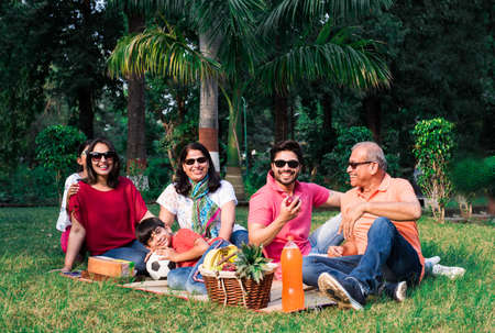 Indian Family enjoying Picnic - Multi generation of asian family sitting over lawn or green grass in park with fruit basket, mat and drinks. selective focus