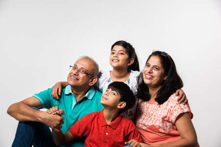 Indian Kids with grandparents smiling while sitting on a white background indoors, selective focus